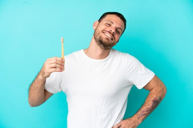 若いブラジル人男性が腰に腕と笑顔でポーズをとって青い背景で隔離の歯を磨く