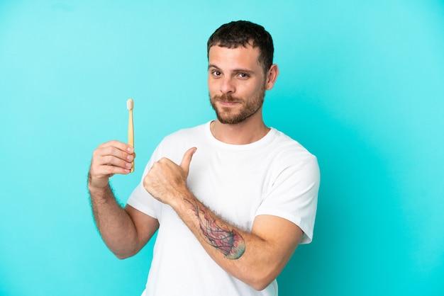 誇りと自己満足の青い背景に分離された歯を磨く若いブラジル人男性