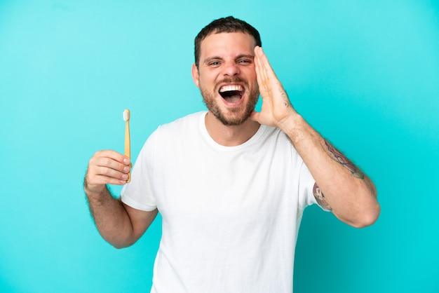 口を大きく開いて叫んで青い背景に分離された歯を磨く若いブラジル人男性