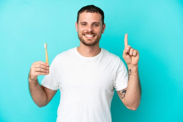 最高の兆候を示して指を持ち上げて青い背景で隔離の歯を磨く若いブラジル人男性