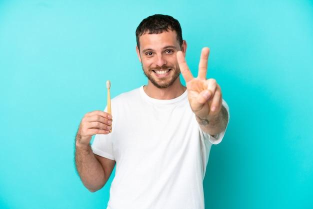 笑顔と勝利の兆候を示す青い背景で隔離の歯を磨く若いブラジル人男性
