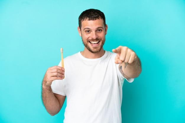 青い背景に分離された歯を磨く若いブラジル人男性は驚いて正面を指しています