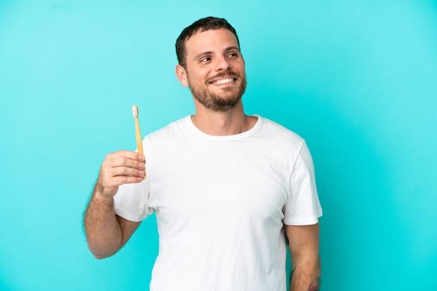 見上げながらアイデアを考えて青い背景で隔離の歯を磨く若いブラジル人男性