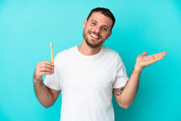 ショックを受けた顔の表情で青い背景に分離された歯を磨く若いブラジル人男性