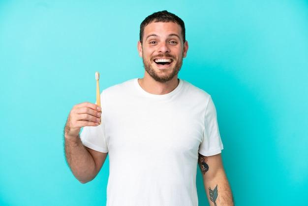 驚きの表情で青い背景に分離された歯を磨く若いブラジル人男性