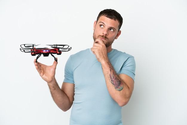 Молодой бразильский мужчина держит дрон на белом фоне и смотрит вверх