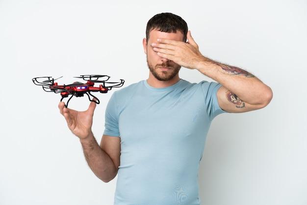 Молодой бразильский мужчина держит дрон, изолированные на белом фоне, закрывая глаза руками. не хочу что-то видеть