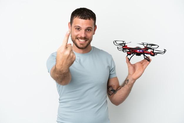 Молодой бразильский мужчина, держащий дрон на белом фоне, делает приближающийся жест