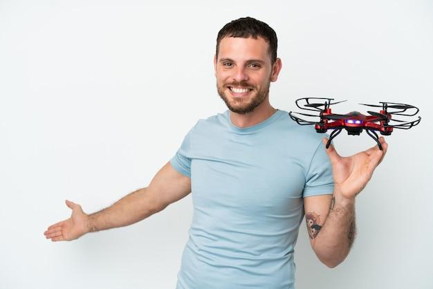 Молодой бразильский мужчина держит дрон на белом фоне, протягивая руки в сторону, приглашая приехать