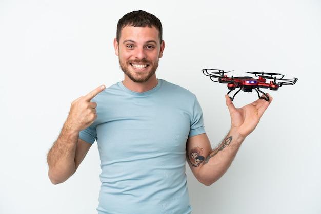 Молодой бразильский мужчина держит дрон, изолированные на белом фоне, показывает палец вверх жест
