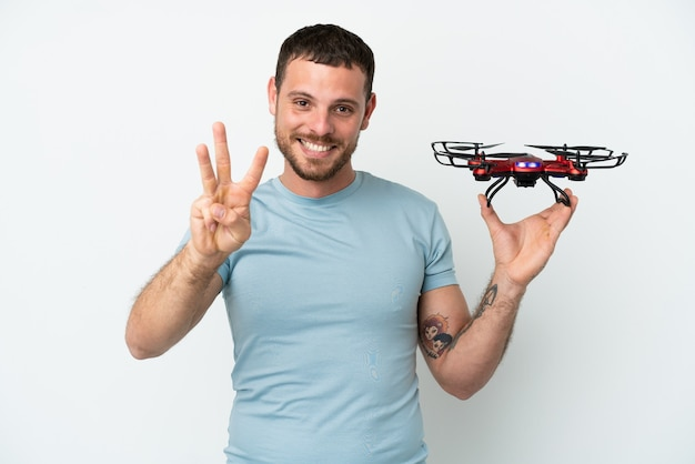 幸せな白い背景で隔離のドローンを保持し、指で3を数える若いブラジル人男性