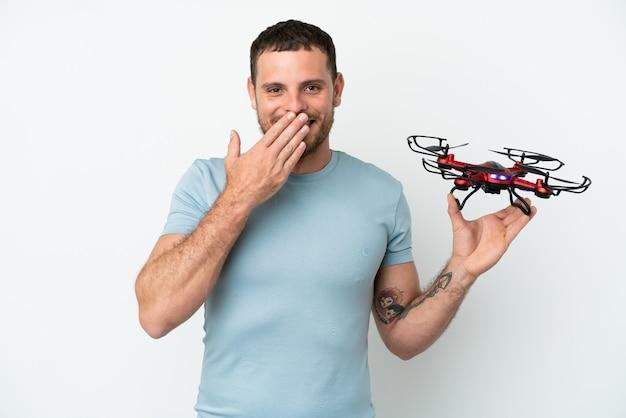 Молодой бразильский мужчина держит дрон, изолированные на белом фоне, счастливый и улыбающийся, прикрывая рот рукой