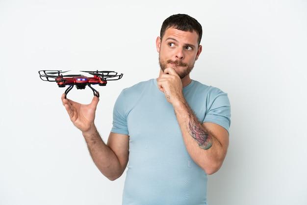 Молодой бразильский мужчина, держащий дрон, изолированный на белом фоне, сомневается и думает