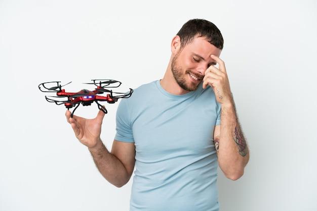 Молодой бразильский мужчина держит дрон, изолированные на белом фоне смеясь