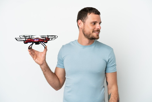 Молодой бразильский мужчина держит дрон на белом фоне смотрит в сторону
