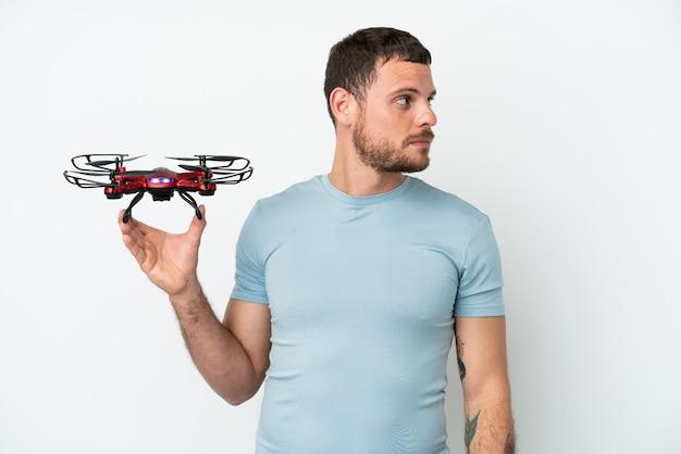Молодой бразильский мужчина держит дрон на белом фоне, глядя в сторону