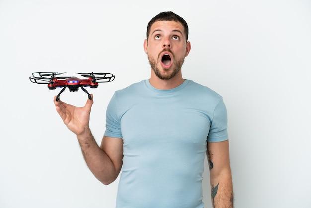 Молодой бразильский мужчина держит дрон на белом фоне, глядя вверх и с удивленным выражением лица