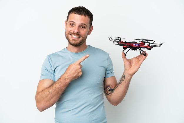 Молодой бразильский мужчина держит дрон на белом фоне, указывая в сторону, чтобы представить продукт