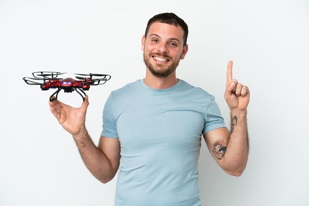 Молодой бразильский мужчина держит дрон на белом фоне, указывая на отличную идею