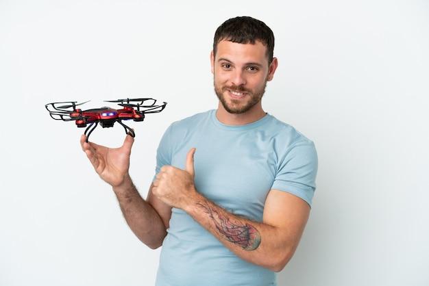 Молодой бразильский мужчина держит дрон на белом фоне, гордый и самодовольный