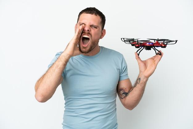 Молодой бразильский мужчина держит дрон на белом фоне и кричит с широко открытым ртом