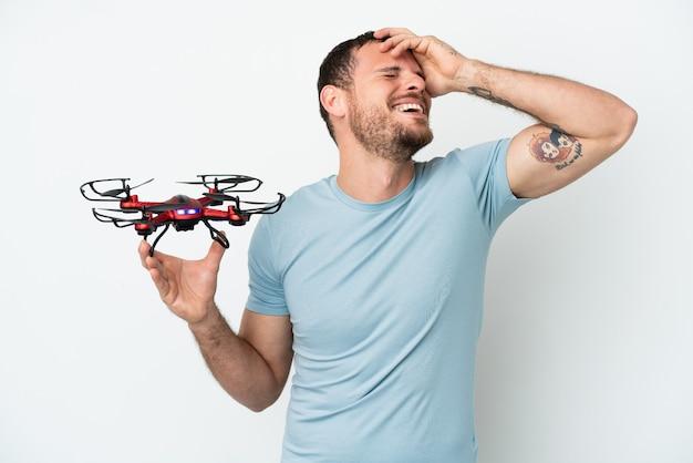 Молодой бразильский мужчина держит дрон на белом фоне, много улыбаясь