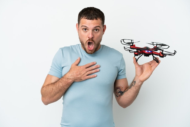 Молодой бразильский мужчина, держащий дрон на белом фоне, удивлен и шокирован, глядя вправо
