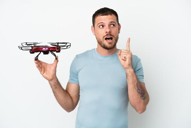 Молодой бразильский мужчина держит дрон на белом фоне, думая об идее, указывая пальцем вверх