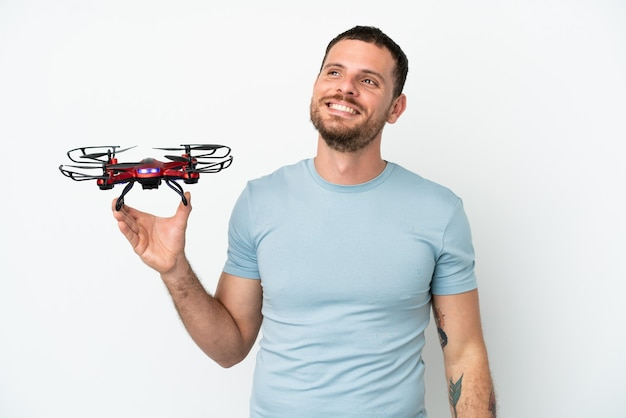 Молодой бразильский мужчина держит дрон на белом фоне, думая об идее, глядя вверх