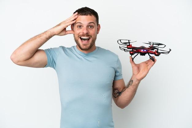 Молодой бразильский мужчина держит дрон на белом фоне с удивленным выражением лица