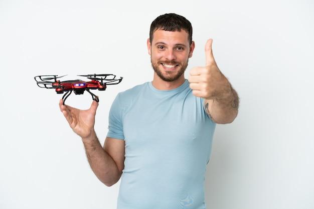 Молодой бразильский мужчина держит дрон на белом фоне с большими пальцами руки вверх, потому что произошло что-то хорошее
