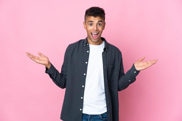 Молодой бразильский мужчина изолирован на розовой стене с удивленным выражением лица