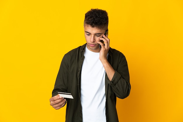 Молодой бразильский мужчина на изолированном фоне, покупающий с мобильного телефона с помощью кредитной карты
