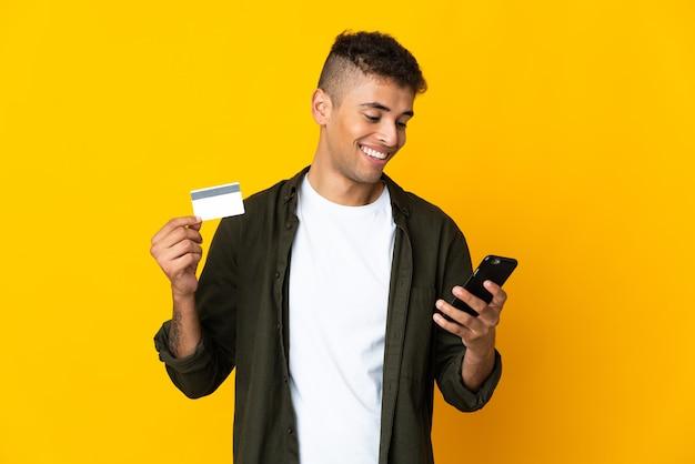 Молодой бразильский мужчина над изолированным пространством покупает мобильный телефон с помощью кредитной карты