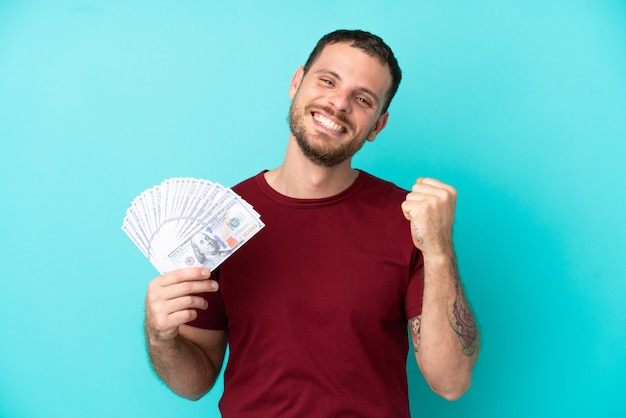 Молодой бразильский мужчина берет много денег на изолированном фоне, празднует победу в позиции победителя