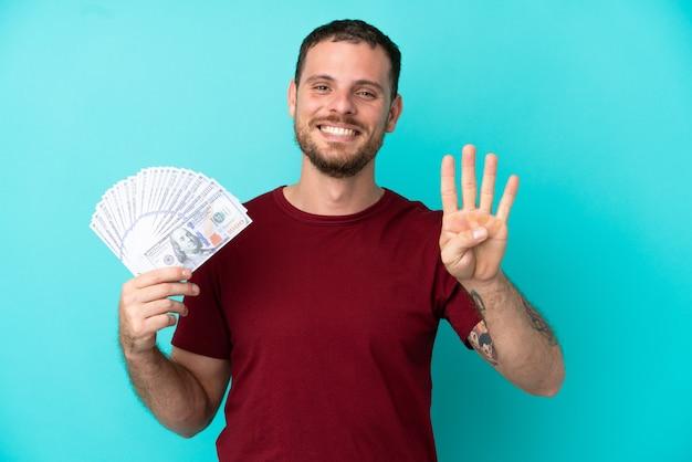 고립된 배경에서 많은 돈을 벌고 있는 젊은 브라질 남자는 행복하고 손가락으로 넷을 세고 있다