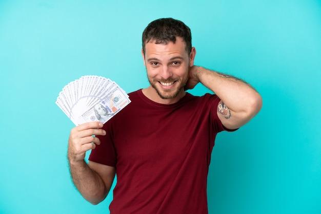 고립된 배경에서 많은 돈을 들고 웃고 있는 젊은 브라질 남자