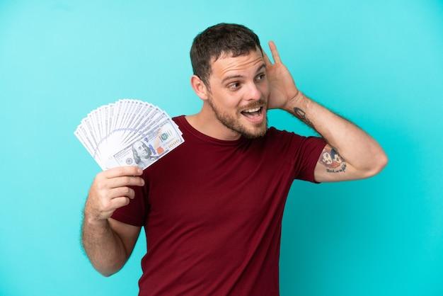 귀에 손을 대고 뭔가를 듣고 고립 된 배경 위에 많은 돈을 복용 하는 젊은 브라질 남자