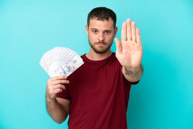 Молодой бразильский мужчина берет много денег на изолированном фоне, делая жест стоп