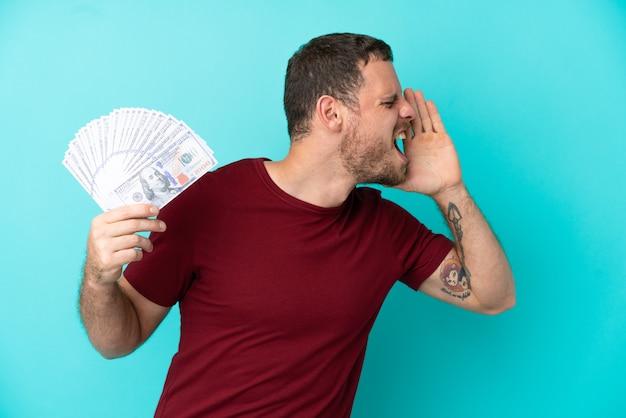 Молодой бразильский мужчина берет много денег на изолированном фоне и кричит с широко открытым ртом