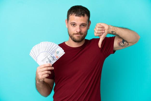 부정적인 표정으로 엄지손가락을 아래로 보여주는 고립된 배경 위에 많은 돈을 복용하는 젊은 브라질 남자