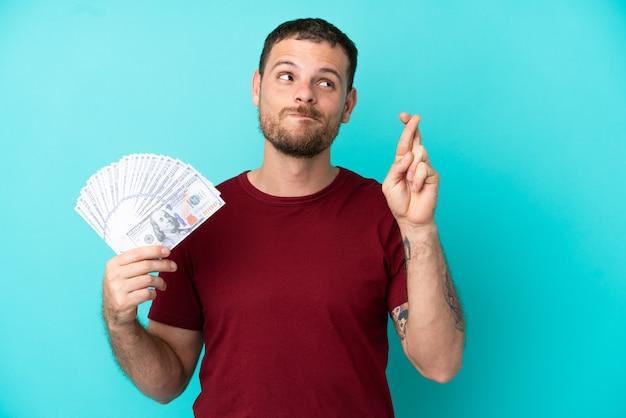 Молодой бразильский мужчина берет много денег на изолированном фоне со скрещенными пальцами и желает всего наилучшего