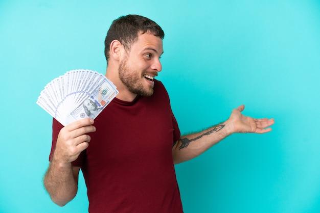 옆을 바라보면서 놀란 표정으로 고립된 배경 위에 많은 돈을 쓰는 젊은 브라질 남자