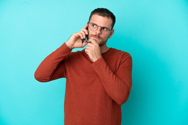 Young brazilian man using mobile phone isolated on blue background and looking up