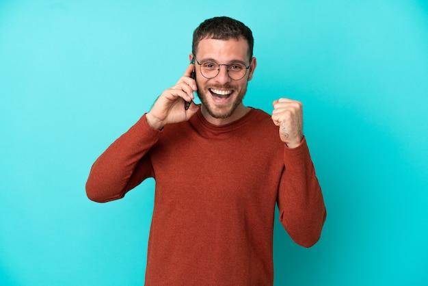 Молодой бразильский мужчина с помощью мобильного телефона на синем фоне празднует победу в позиции победителя