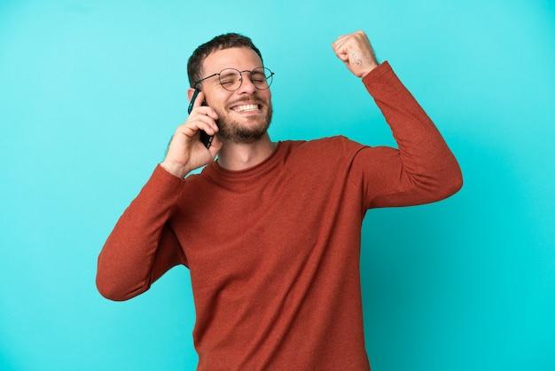 Молодой бразильский мужчина с помощью мобильного телефона на синем фоне празднует победу