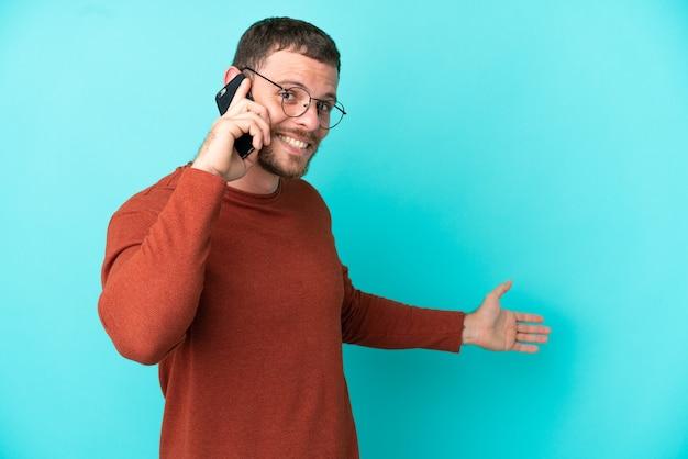 Молодой бразильский мужчина с помощью мобильного телефона изолирован на синем фоне, протягивая руки в сторону, чтобы пригласить приехать