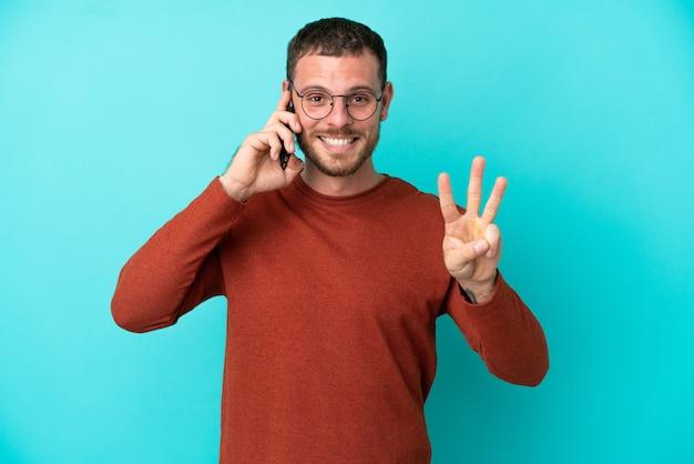 Молодой бразильский мужчина с помощью мобильного телефона, изолированного на синем фоне, счастлив и считает три пальцами