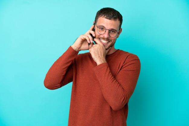 Молодой бразильский мужчина с помощью мобильного телефона, изолированных на синем фоне, счастлив и улыбается