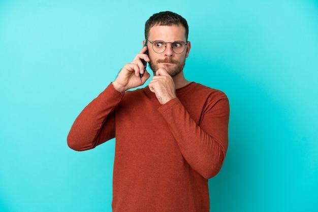 Молодой бразильский мужчина с помощью мобильного телефона изолирован на синем фоне, сомневаясь и думая